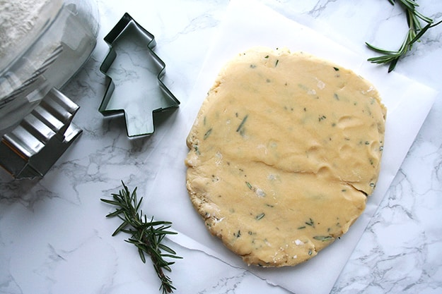 rosemary shortbread cookie dough, cookie cutters, and sprigs of rosemary
