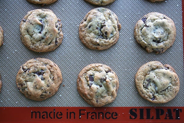 perfectly spaced salted chocolate chunk cookies on a silpat baking sheet