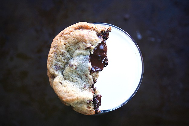 a melty salted chocolate chunk cookie on top of a glass of milk