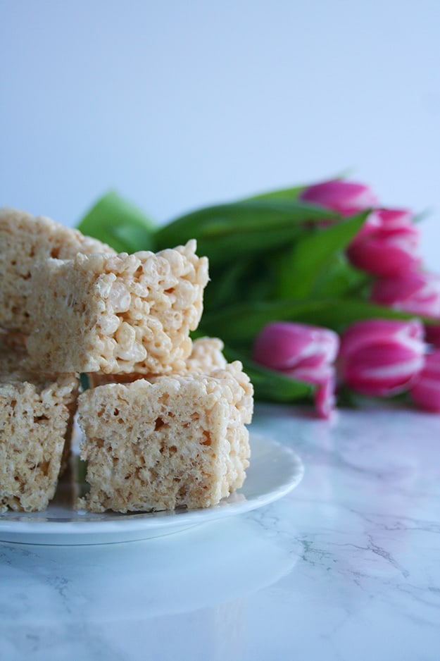 a close up shot of an in focus plate of browned butter Rice Krispie treats with pink tulips out of focus in the background