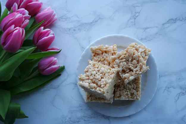 looking down from above at a plate of browned butter Rice Krispie treats and a bunch of pink and white tulips on a carrara marble counter