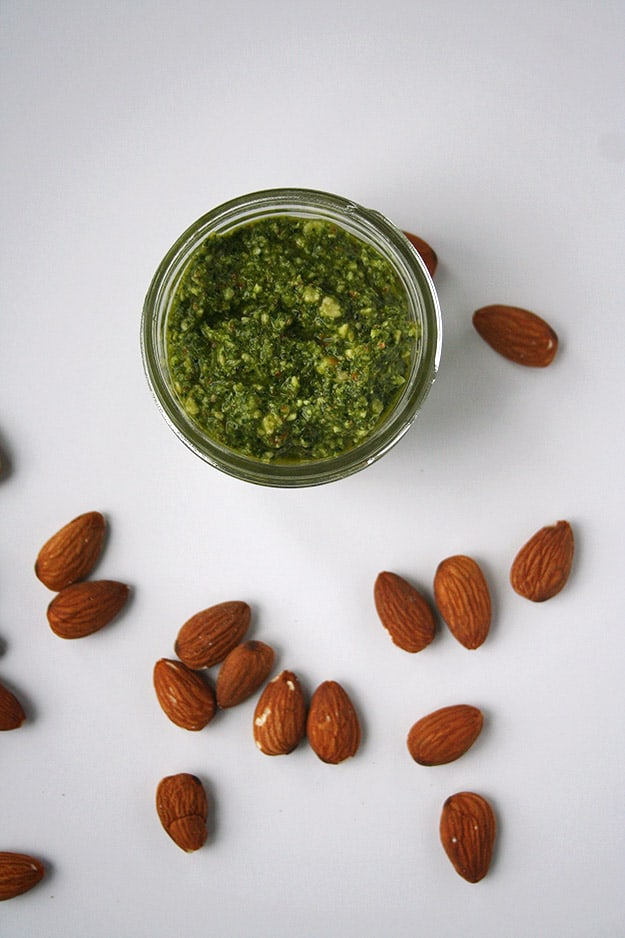 an overhead shot of this ultra green kale almond pesto in a glass jar on a blank white canvas covered in out of focus almonds