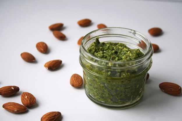 kale almond pesto in a clear glass jar on a white canvas with almonds sprinkled around