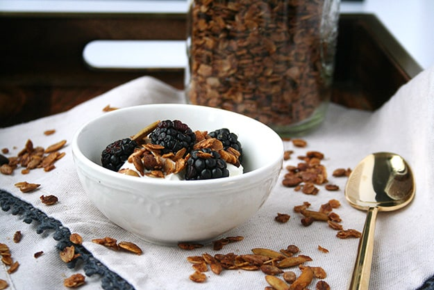 a bowl of greek yogurt in the foreground topped with blackberries and olive oil pistachio granola