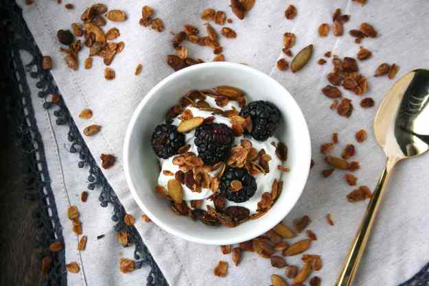 an overhead shot of greek yogurt topped with blackberries and olive oil pistachio granola on a cream napkin covered in granola spinkles