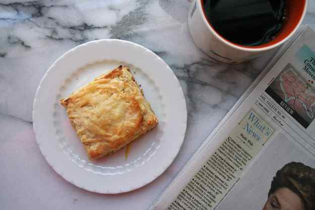 an overhead shot of an apple and white cheddar square scone on a round plate with the Wall Street Journal and a cup of black coffee