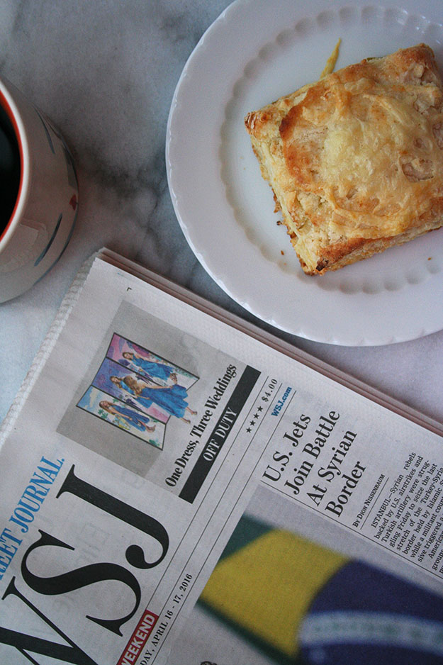 an overhead shot of an apple and white cheddar scone with the WSJ and a cup of coffee on carrara marble