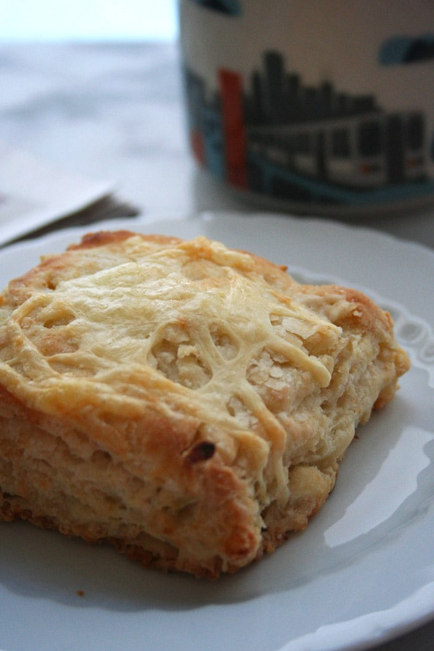 a zoomed in shot of an apple and white cheddar scone with melted cheddar cheese on top