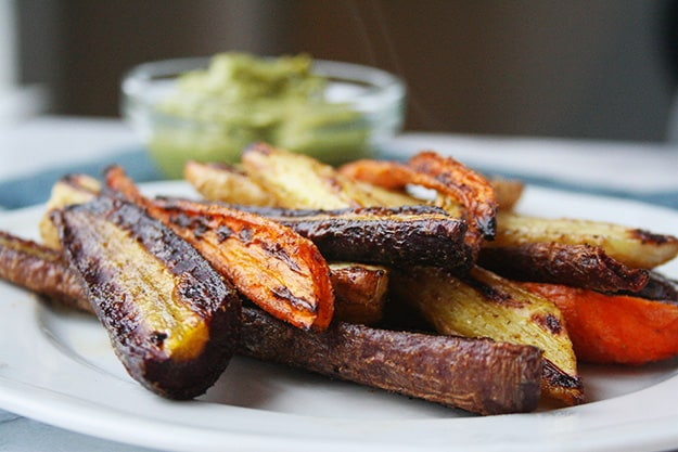 an eye level view of roasted rainbow carrots on a white plate with magic green sauce out of focus in the background
