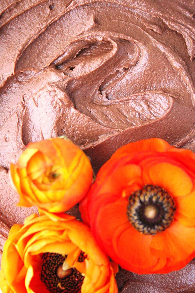 an close up shot of the chocolate tahini frosting with decorative orange ranunculus flower on a tahini cake