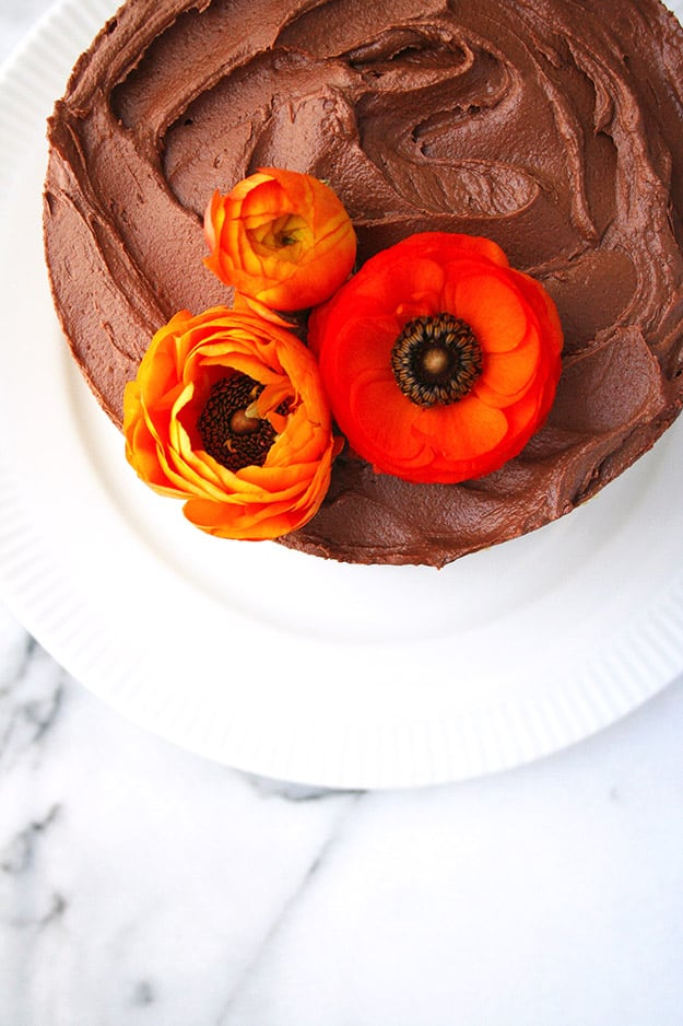bright orange ranunculus flowers sit on top of a tahini cake with chocolate tahini frosting for decoration