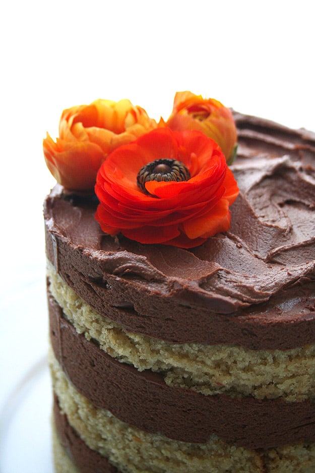tahini cake with chocolate tahini frosting with orange ranunculus flowers on top