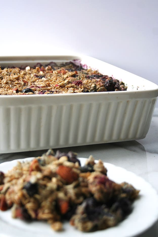 an out of focus plate of triple berry baked oatmeal in the foreground with an in focus baking dish filled with triple berry baked oatmeal in the background