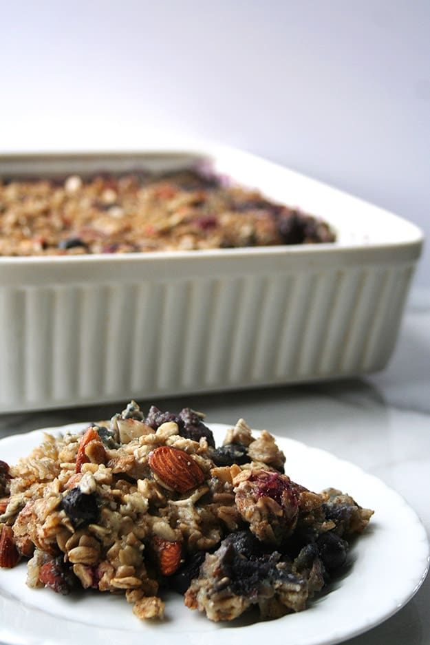 an in focus plate of triple berry baked oatmeal in the foreground with an out of focus baking dish filled with triple berry baked oatmeal in the background