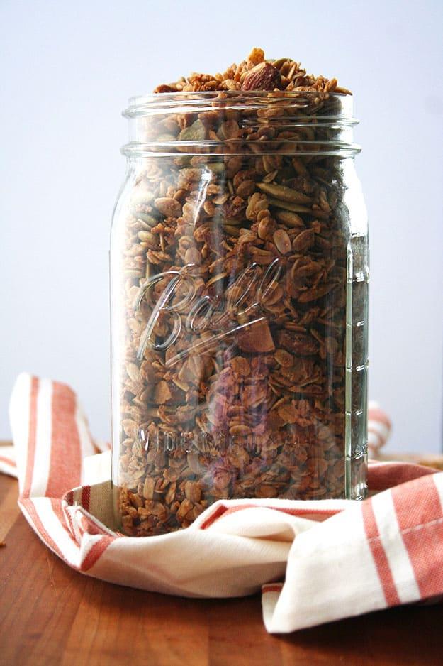 a glass Ball jar full of maple tahini granola on a cream and orange striped napkin
