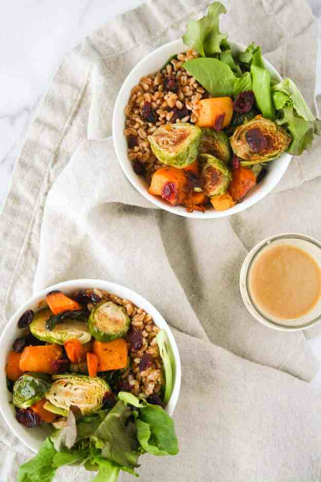 The perfect fall dinner - Autumn Grain Bowls with Farro, Roasted Butternut Squash and Brussels Sprouts, Dried Cranberries, and a Maple-Tahini Dressing! These bowls come together in a flash and are easy to meal prep over the weekend. | Hungry by Nature