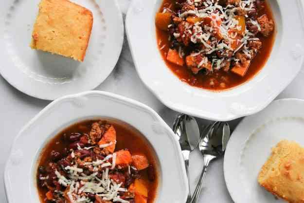 overhead shot of bowls of crockpot turkey chili with sweet potatoes and cornbread