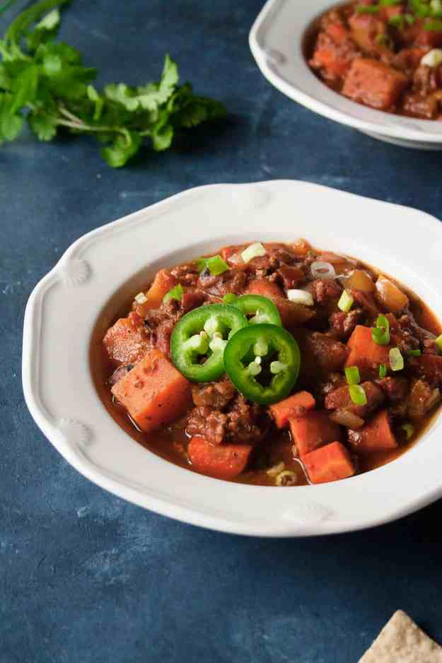 bowl of Paleo Pumpkin Turkey Chili on blue background with jalapeno slices