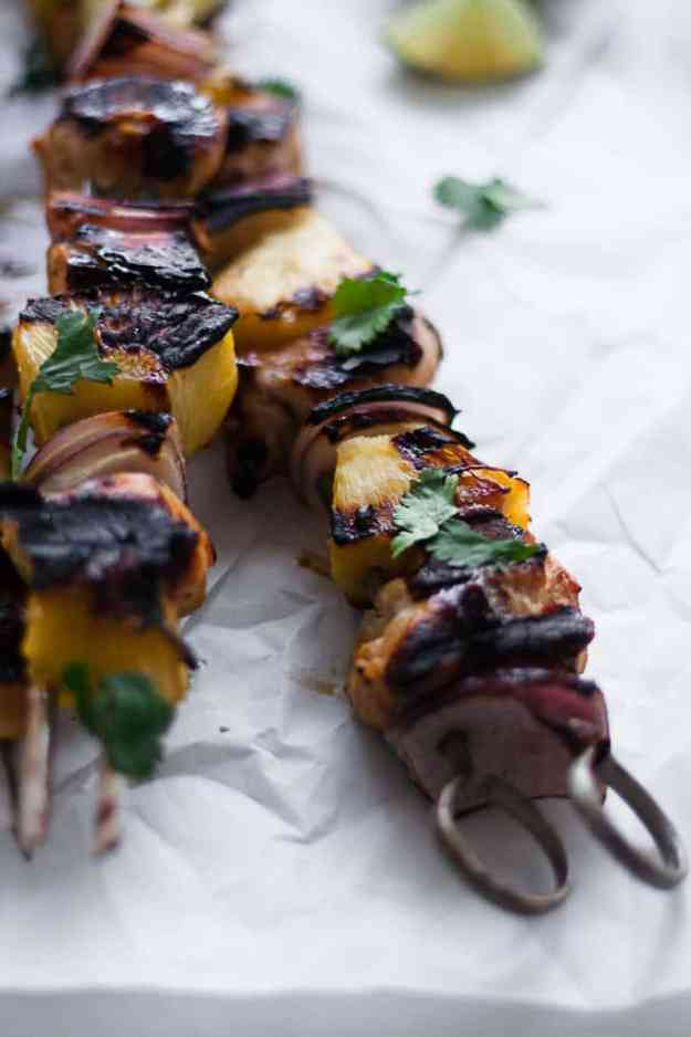 close up shot of hawaiian chicken kebabs with red onion, pineapple, cilantro, and lime wedges
