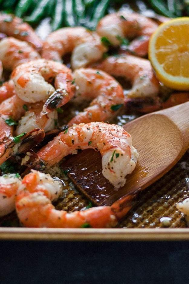 close up shot of sheet pan shrimp and green beans with a lemon wedge