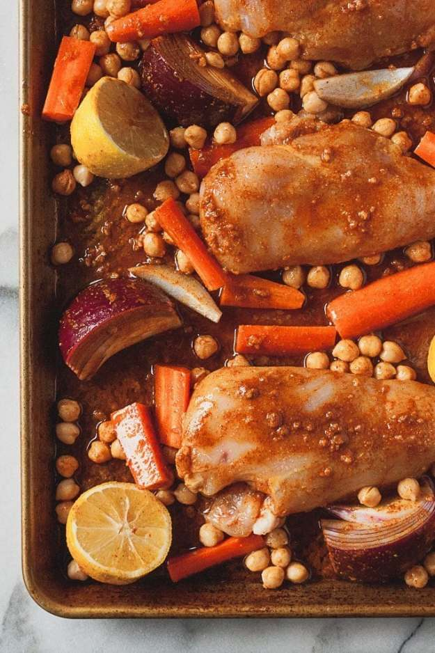 overhead shot of chicken breast on sheet pan with chickpeas carrots and red onions - sheet pan moroccan chicken