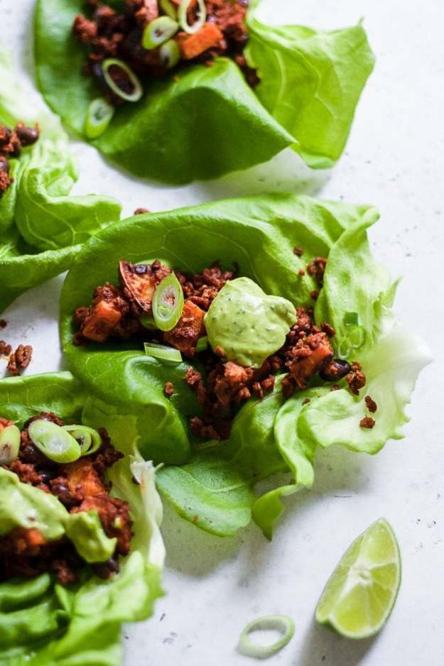 Trader Joe's soy chorizo lettuce wraps with avocado lime sauce, fresh limes, and sliced green onions