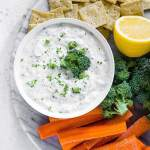 dairy free tzatziki sauce no dill in a bowl on a platter with crackers and vegetables