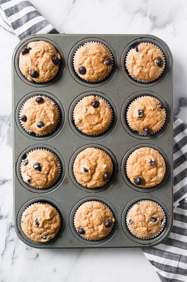 gluten free blueberry muffins in muffin tin with striped napkin