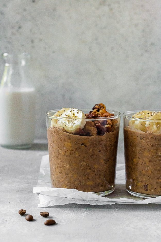espresso overnight oats with banana slices in glasses with a jar of milk in the background