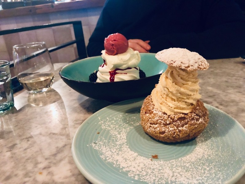 Blackberry Pavlova and Praline Choux against marble table at Rocket and Ruby restaurant in Liverpool