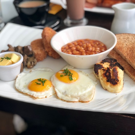 Vegetarian breakfast on white plate with baked beans, halloumi, brown toast, hash browns, two fried eggs and a small bowl of butter