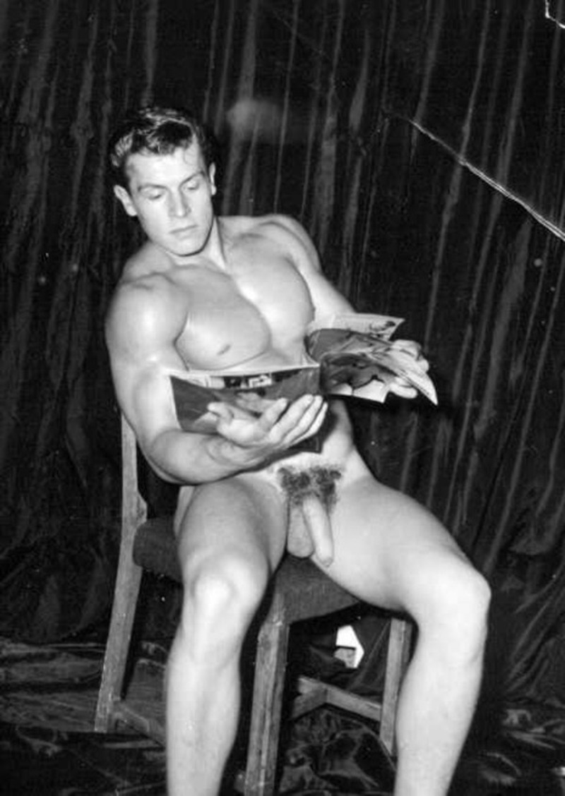 hung physique model Helmut Riedmeier looking through a magazine with his long dick on show