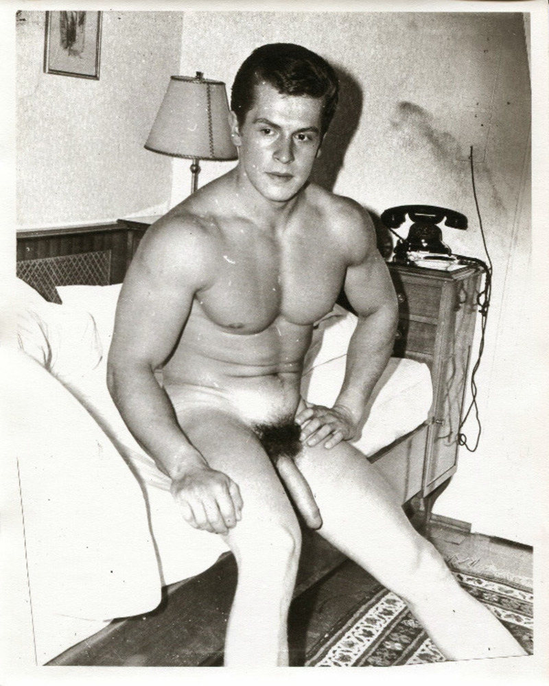 Naked model Helmut Riedmeier showing his long uncut cock while sitting on a bed