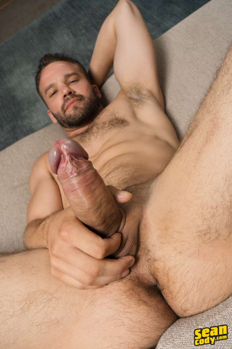 handsome bearded hunk laying on a couch and holding his thick and hard uncut cock for the camera