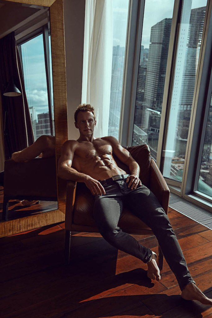 Handsome shirtless model Andrey Pavlov in a chair wearing jeans