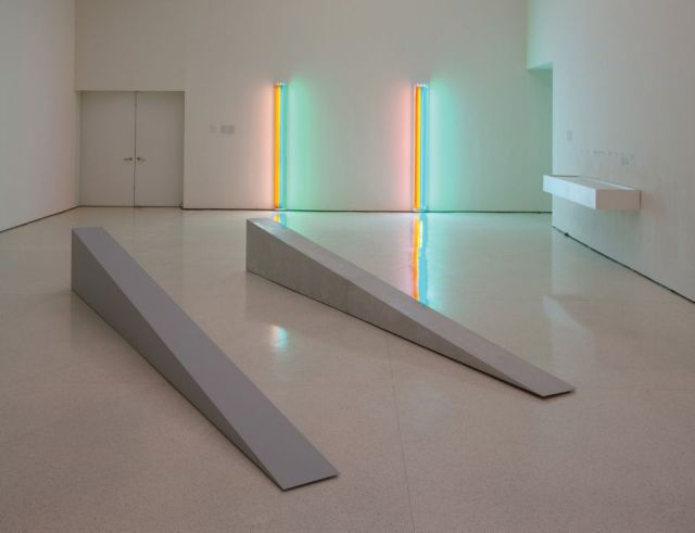 In foreground, two fabrications of Robert Morris's Untitled (Door Stop), 1965. (On left: 2018 artist-supervised, museum-made plywood fabrication; on right: 1965 fiberglass fabrication).  On far wall: two fabrications of Dan Flavin's Untitled (to Henri Matisse) 1964. (On left: historical fabrication received from Panza; right: 1995 fabrication produced in coordination with the Flavin studio)
