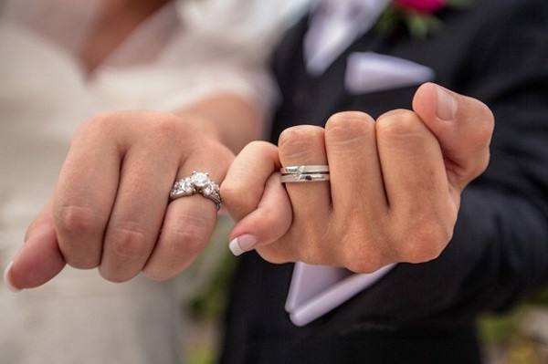 Couple holding hands with wedding ring in it