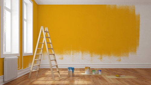 A wall is half painted with cans of paint and a ladder scattered through the room.