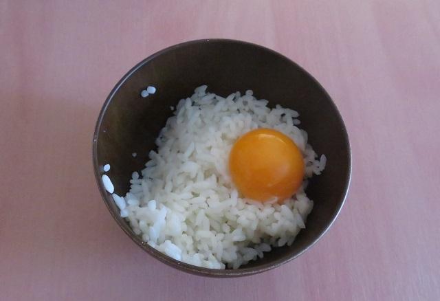 生卵の黄身をごはんにのせた写真