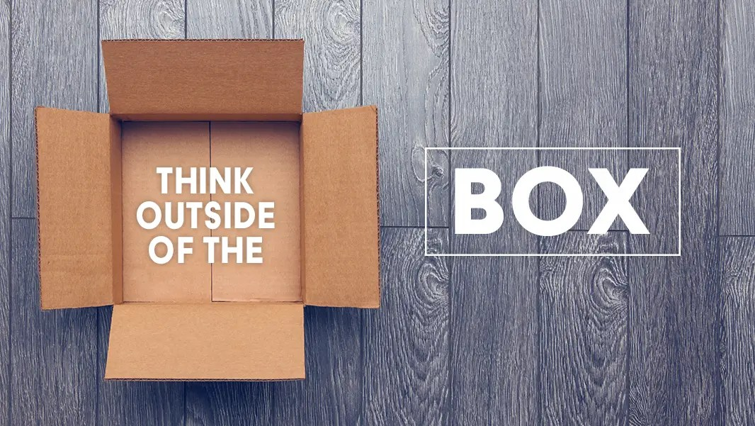 Think Outside of the Box; cardboard box on a wooden floor background