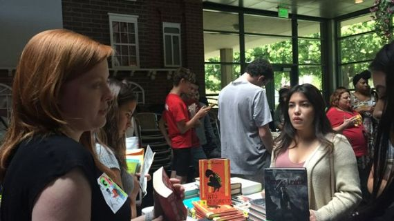 Volunteers give out books to foster care students