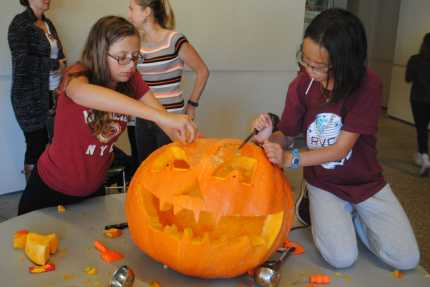 A huge pumpkin is being carved by two students. Credit: Luke Schneider '20 / SPECTRUM