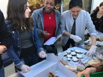 Coco Kaleel '20, Skylar Graham '20 and Yoohan Ko '20 help sell baked goods. Credit: Astor Wu '20/SPECTRUM