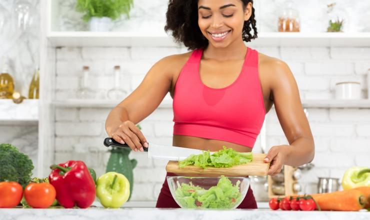 Beautiful young black girl preparing vegetable salad at home