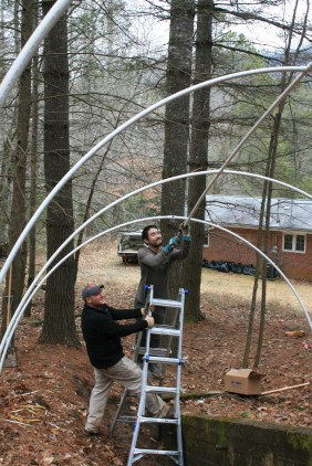 Brian supporting Raymond, while he pounds in PVC pipe for the structure of the hoop-house.