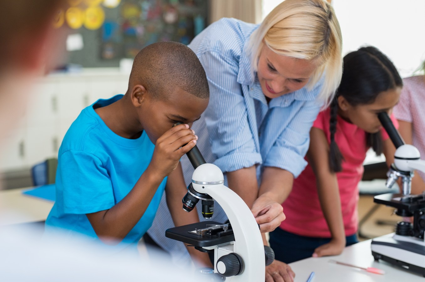 Multiethnic pupils looking through microscope at primary school. Happy elementary students in biology class analyzing cells through microscope. Children with teacher making chemical experiment in laboratory.