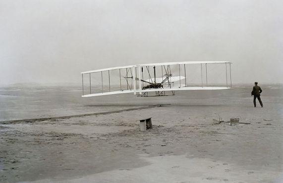 """Kill Devil Hills (near Kitty Hawk, North Carolina): First flight of the """"Wright Flyer I"""", 17 Dec 1903, Orville piloting, Wilbur running at wingtip."""