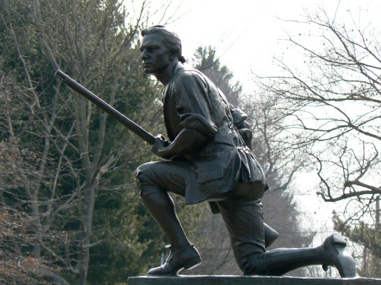 """The Westport (Connecticut) Minuteman monument kneels atop a traffic circle at the intersection of Compo Road South and Compo Beach Road. The monument depicts a musket-wielding Continental soldier waiting with his sleeves rolled up for the returning Redcoats. A plaque on the north side of the base reads """"To commemorate the heroism of the patriots who defended their country when the British invaded this state April 25th 1777. General David Wooster, Colonel Abraham Gould and more than one hundred Continentals fell in the engagements commencing at Danbury and closing on Compo Hill"""". The monument was created by sculptor Harry Daniel Webster and was cast by Tiffany Studios in 1910."""