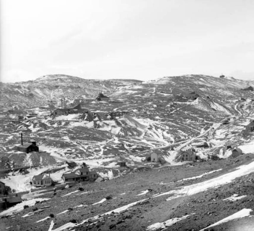Several mines dot Gunnell Hill in Central City, Colorado. Patches of snow also line the hillside. A row of small houses stands in the foreground. (Denver Public Library Digital Collections, 1899?)