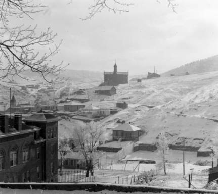 """The side of the Gilpin County Courthouse stands in the left foreground in this view looking toward the St. Aloysius Academy, a Catholic school on Gunnell Hill in Central City, Colorado. Snow covers the ground after the """"Big Snow"""" in December of 1913. The steeple of St. Mary's Catholic Church is in the left background. (Denver Public Library Digital Collections, 1913)"""